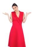 Hesitant elegant brunette in red dress posing Royalty Free Stock Images