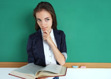 Hesitant girl with open book thinking and looking towards. Royalty Free Stock Image