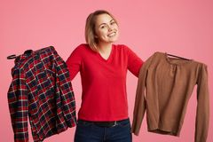 Hesitant lovely young female holds in hands two shirts, can`t choose which to buy, looks positively into camera, likes shopping, i royalty free stock photos