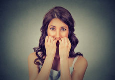 Hesitant nervous woman biting her fingernails craving for something or anxious. Closeup portrait young unsure hesitant nervous woman biting her fingernails Royalty Free Stock Photo
