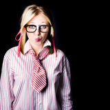 Hesitant uncertain smart business girl on black. Confused and unsure business girl pouting in a business uncertainty concept on black background Royalty Free Stock Photo