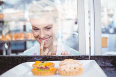 Hesitating pretty woman looking at fruit pie Royalty Free Stock Photography