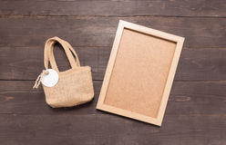 Hessian η τσάντα σάκων με το πλαίσιο ετικεττών και εικόνων είναι στο ξύλινο BA Στοκ Εικόνα