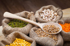 Hessian bags with dry grains. Hessian bags with dry peas, chick peas, red lentils, wheat and green mung on kitchen table royalty free stock photo