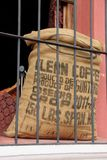Hessian Coffee Bag. A Hessian Coffee Bag standing in a window with iron bars at a shop in Antigua, Guatemala stock photo