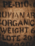 Hessian fabric stamped organic. Vertical background of a twenty kilogram hessian coffee bag stamped and certified one hundred percent organic Stock Image