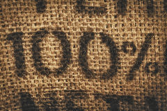 Hessian one hundred percent background. Background of woven textured hessian stamped with one hundred percent - 100 percent - in numerals Stock Photography