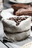 Hessian sack of coffee beans on old grey wooden table. Stock Photo