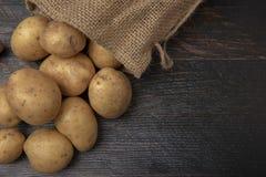 Hessian sack filled with organic potatoes stock photos