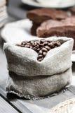 Hessianssäck av kaffebönor på den gamla gråa trätabellen. arkivfoto