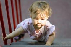 Het éénjarige kind beklimt op de treden Stock Afbeelding