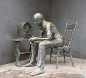 Het 'Hoekje bij de haardpraatje '- brons standbeeld van een mens die aan radio tijdens grote depressie luisteren stock foto's