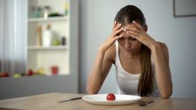 Het aan anorexie lijdende meisje voelt duizelig, uitgeput door strenge diëten, uitgeput lichaam, verhongering stock fotografie