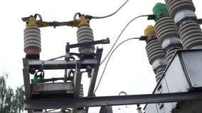 Het aanaarden schakelen en de lijn van de elektriciteitstransmissie op een berk en een heldere hemelachtergrond Kader Het aanaard stock footage