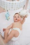 Het aanbiddelijke baby spelen met speelgoed in voederbak royalty-vrije stock fotografie