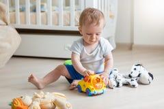 Het aanbiddelijke babyjongen spelen met stuk speelgoed auto op vloer bij woonkamer stock foto's