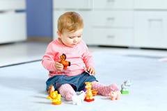 Het aanbiddelijke babymeisje spelen met binnenlandse stuk speelgoed huisdieren zoals koe, paard, schapen, hond en wilde dieren zo stock fotografie