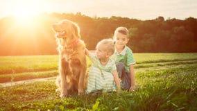 Het aanbiddelijke broer en zuster spelen met hun huisdierenhond Stock Fotografie