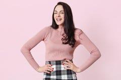 Het aanbiddelijke donkere haired meisje in roze overhemdsnad controleerde rok, die met handen stellen op heupen, lachend terwijl  stock afbeelding