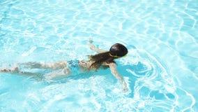 Het aanbiddelijke gelukkige meisje geniet van zwemmend in de pool De vakantie van de familiezomer, jong geitje ontspant bij pool stock footage