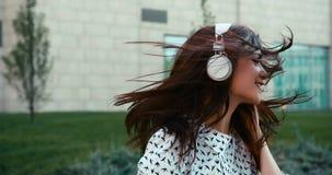 Het aanbiddelijke het glimlachen brunette geniet van de muziek in haar witte hoofdtelefoons openlucht De gelukkige jonge zakken v stock video