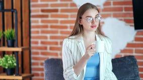 Het aanbiddelijke glimlachende bedrijfsvrouw denken en het drinken koffie bij het moderne middelgrote schot van het zolderbureau stock videobeelden
