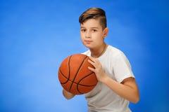 Het aanbiddelijke kind van de 11 éénjarigenjongen met basketbalbal Stock Foto