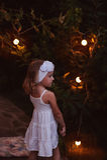 Het aanbiddelijke kindmeisje in witte die kleding en hoofdbandholding boekt in de tuin van de de zomeravond met lichten wordt ver Stock Fotografie
