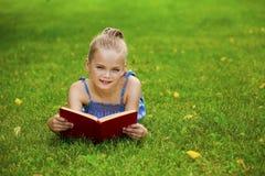 Het aanbiddelijke leuke boek van de meisjelezing buiten op gras Stock Foto's