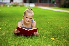 Het aanbiddelijke leuke boek van de meisjelezing buiten op gras Stock Afbeelding