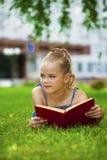 Het aanbiddelijke leuke boek van de meisjelezing buiten op gras Royalty-vrije Stock Foto's