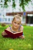 Het aanbiddelijke leuke boek van de meisjelezing buiten op gras Stock Afbeeldingen