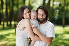 Het aanbiddelijke mamma, de knappe vader en hun prachtige kleine dochter gekleed in de witte enkel kleren omhelzen in stock afbeelding
