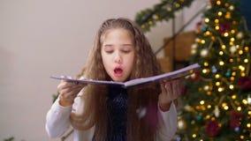 Het aanbiddelijke meisje blazen schittert confettien van boek stock videobeelden