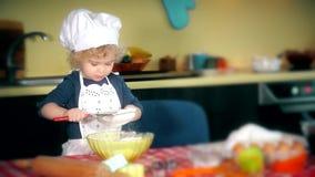 Het aanbiddelijke meisje die van de keukenchef-kok bloem voor cake ziften stock videobeelden