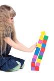 Het aanbiddelijke meisje duwt een baksteenstuk speelgoed toren   Stock Afbeeldingen
