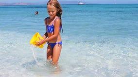 Het aanbiddelijke meisje heeft pret met strandspeelgoed in ondiep water bij tropisch strand stock videobeelden