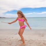 Het aanbiddelijke meisje heeft pret in ondiep water bij royalty-vrije stock foto