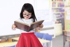 Het aanbiddelijke meisje leest boek in klasse Royalty-vrije Stock Foto's