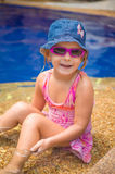 Het aanbiddelijke meisje met roze zonnebril en de blauwe hoed zitten in pool op s Stock Afbeeldingen