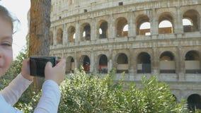 Het aanbiddelijke meisje neemt foto's op smartphone dichtbij Colloseum in Rome