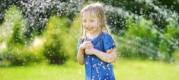 Het aanbiddelijke meisje spelen met een sproeier in een binnenplaats op zonnige de zomerdag Leuk kind die pret met water hebben i stock fotografie
