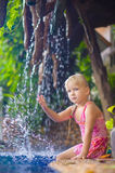 Het aanbiddelijke meisje zit en bespattend aan poolkant met kleine waterfal Stock Foto
