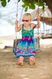 Het aanbiddelijke meisje in zonnebril zit op kabelschommeling onder palmen o royalty-vrije stock foto's