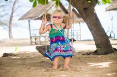 Het aanbiddelijke meisje in zonnebril zit op kabelschommeling onder palmen o royalty-vrije stock afbeelding