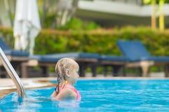 Het aanbiddelijke meisje zwemt dichtbij ladder in pool in tropische strandtoevlucht Royalty-vrije Stock Afbeeldingen