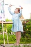 Het aanbiddelijke peutermeisje schilderen op de schildersezel in de tuin Stock Foto's