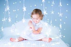 Het aanbiddelijke peutermeisje spelen met haar stuk speelgoed draagt in een witte slaapkamer tussen Royalty-vrije Stock Foto