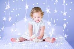 Het aanbiddelijke peutermeisje spelen met haar stuk speelgoed draagt tussen zachte lichten in stervorm Royalty-vrije Stock Foto