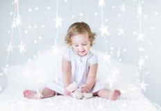 Het aanbiddelijke peutermeisje spelen tussen Kerstmislichten Stock Afbeeldingen